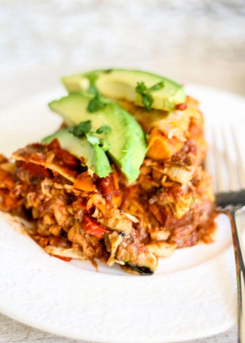 Vegetarian tortilla pie on a plate topped with avocado
