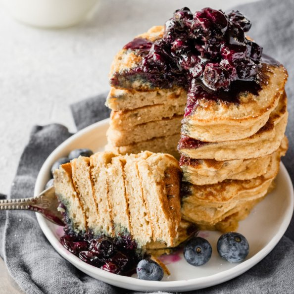 paleo banana coconut flour pancakes in a stack topped with blueberry maple syrup