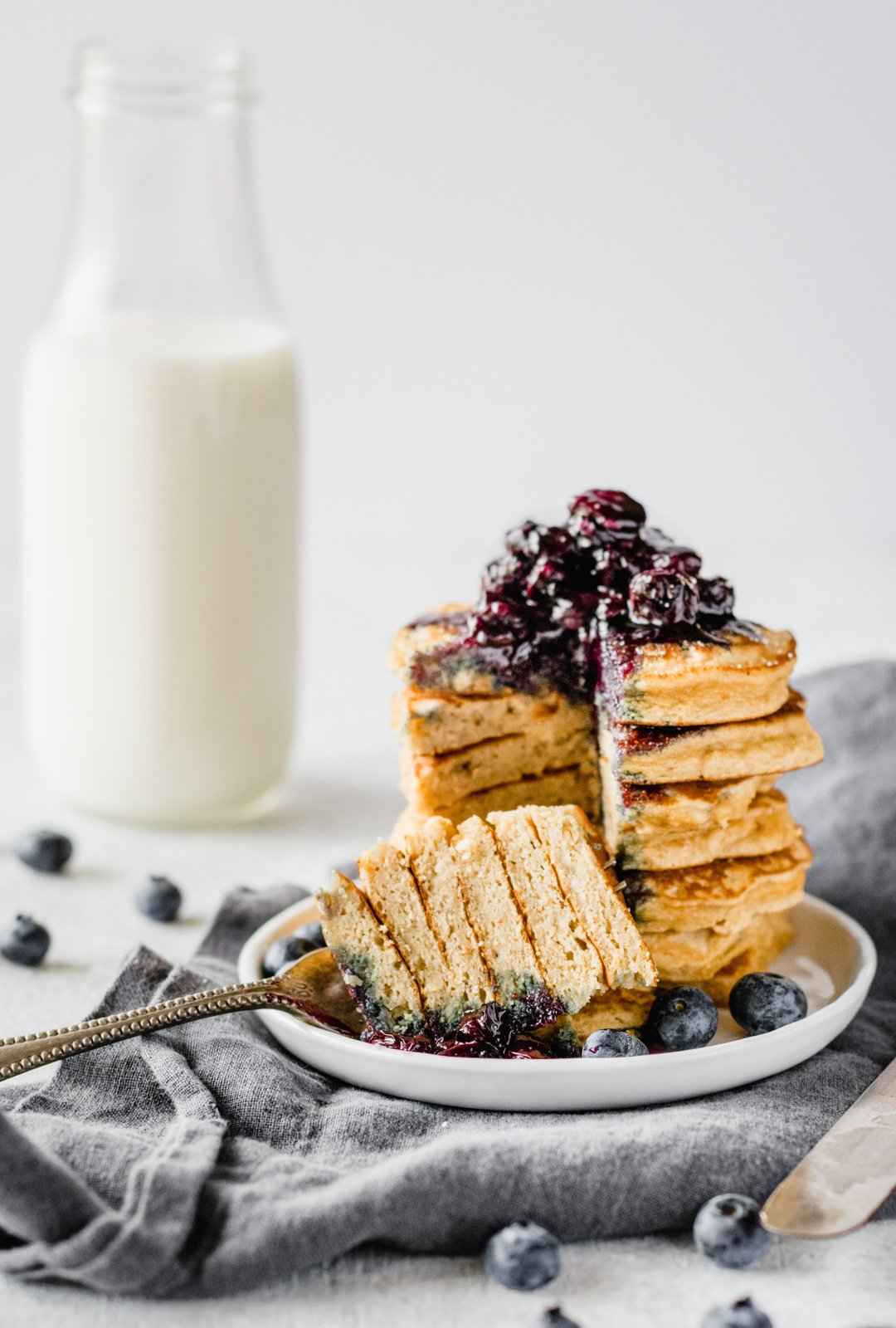 stack of dairy free coconut flour pancakes with blueberry syrup and a bottle of milk in the background