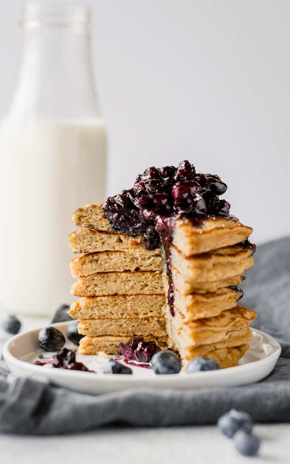 stack of paleo pancakes with blueberry syrup on top and bottle of milk in the background