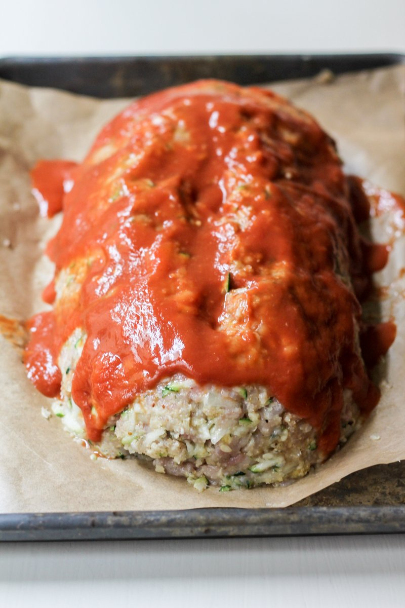 : turkey zucchini meat loaf stuffed with cheese and topped with red sauce