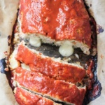 turkey zucchini meat loaf stuffed with cheese and topped with red sauce