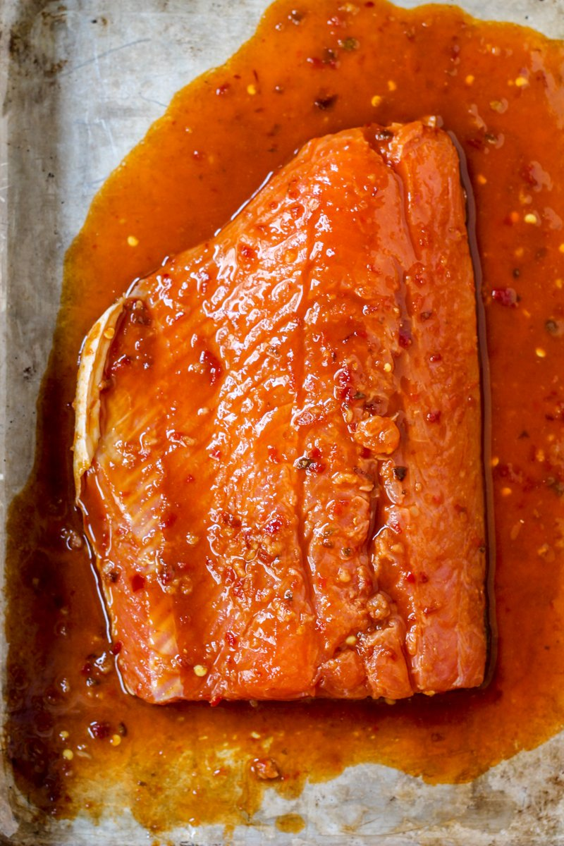 piece of salmon marinating in honey and sriracha