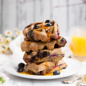 stack of paleo waffles with blueberries with maple syrup