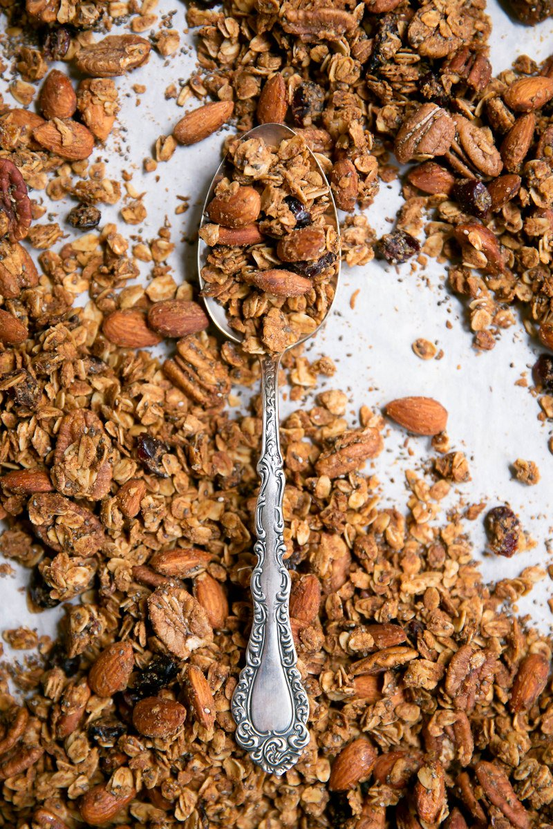 A spoon covered in almonds, oats, raisins and nuts