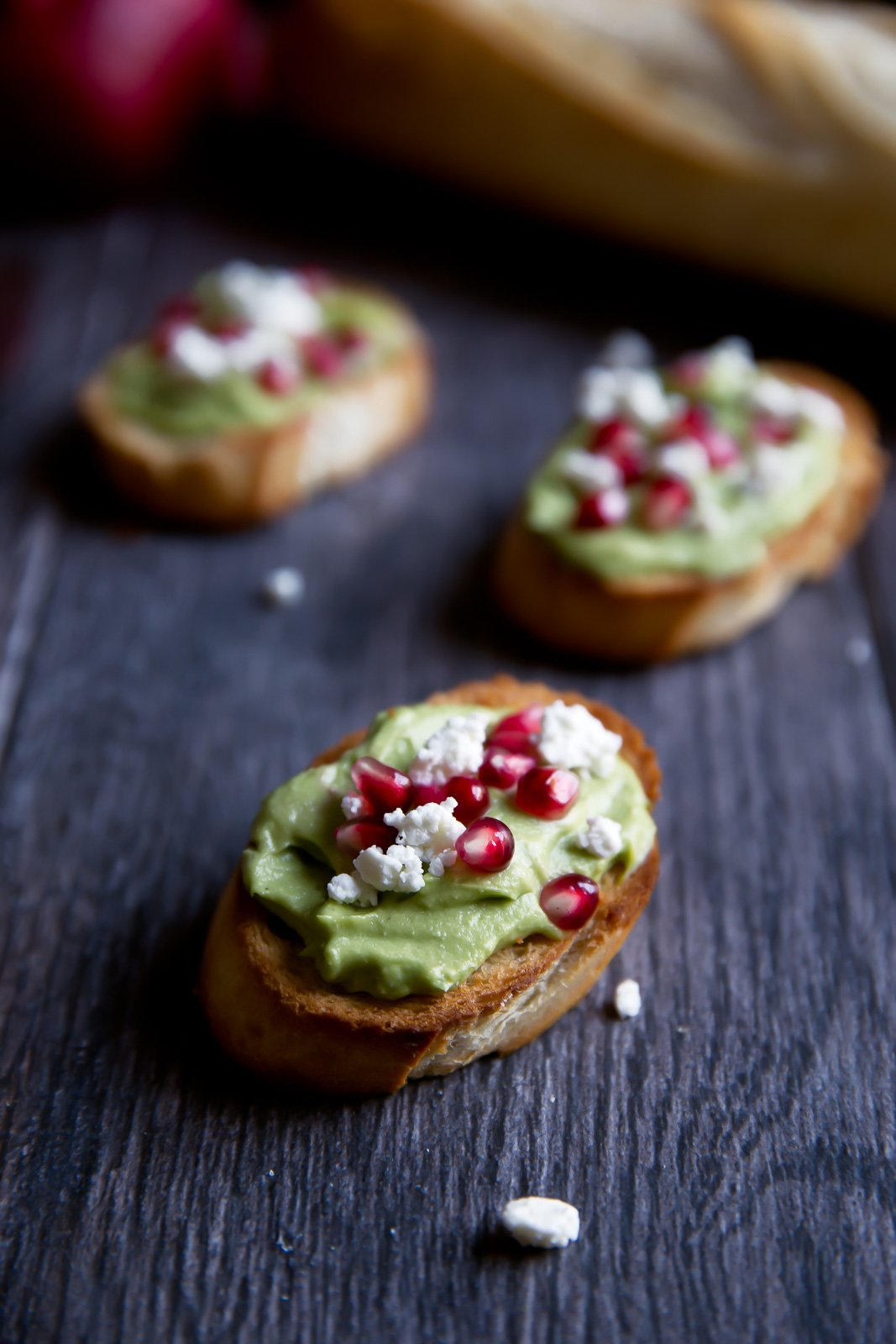 avocado crostini topped with feta and pomegranate seeds