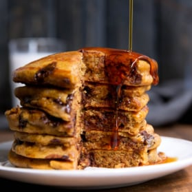 stack of whole wheat pumpkin chocolate chip pancakes with maple syrup