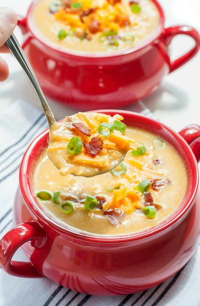 bowls of sweet potato and cauliflower soup with cheese and bacon