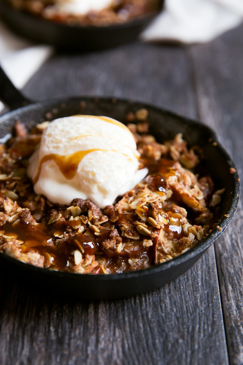 caramel apple crisp in skillet with scoop of ice cream on top