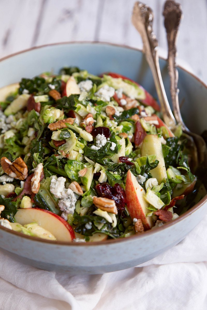 bowl of shredded brussels sprouts salad with apple, pecans, and cheese