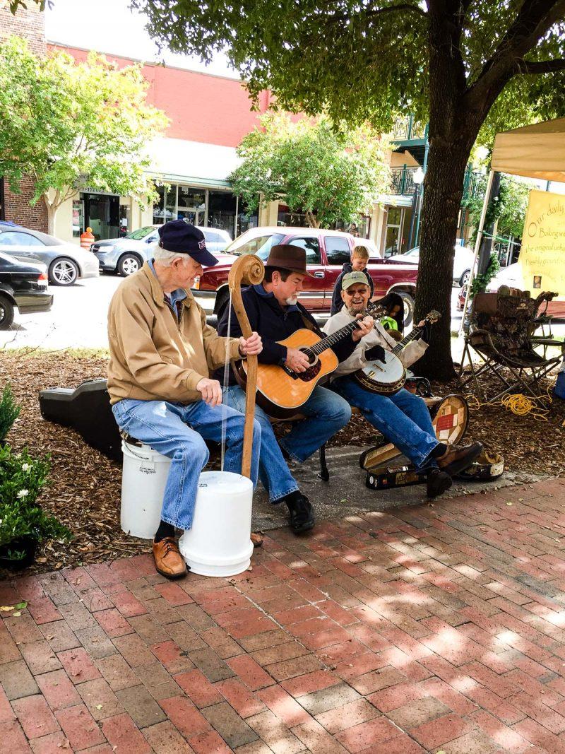 three men playing instruments at outdoor market
