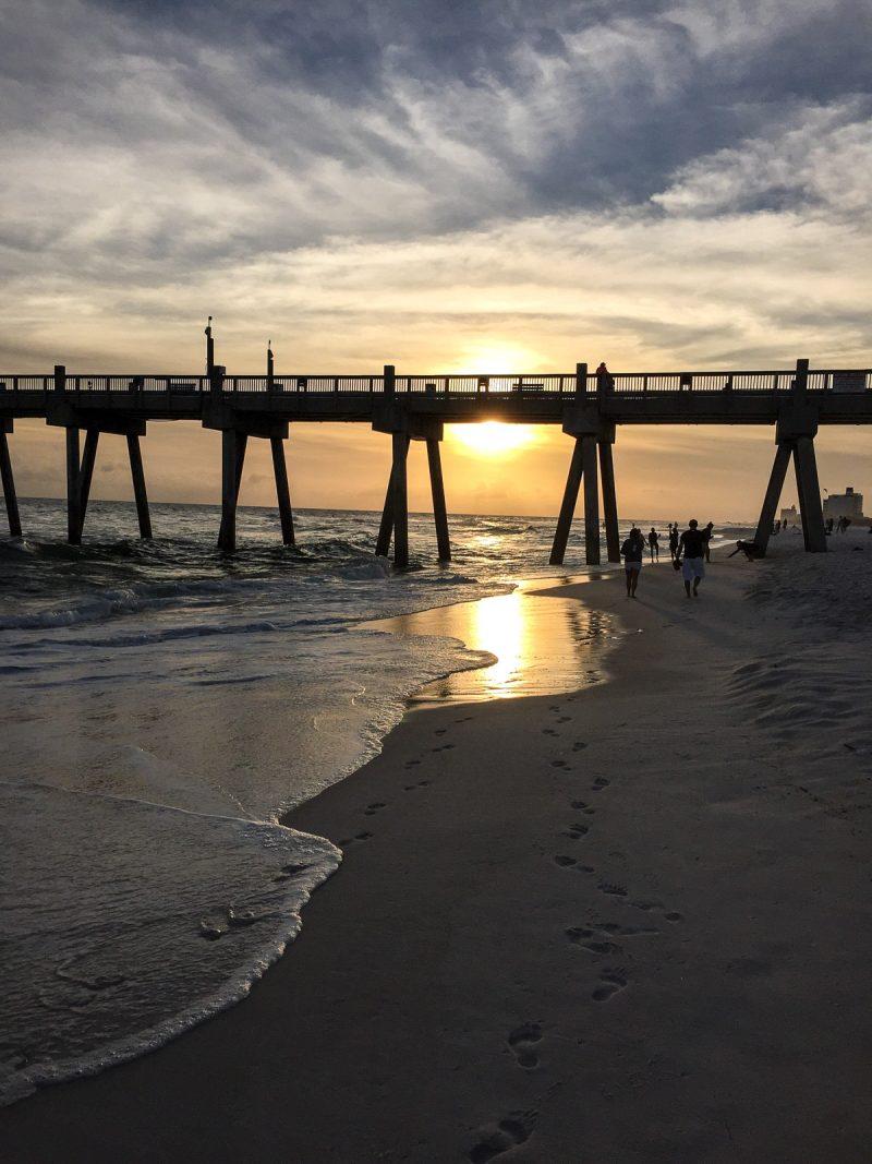 sunset behind pier at ocean beach
