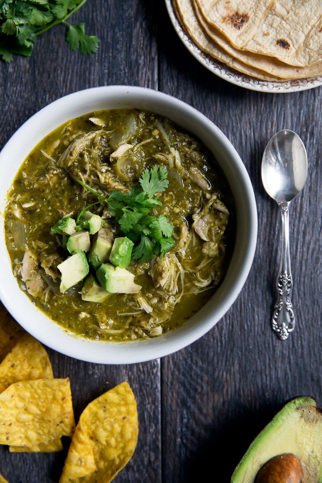Green chicken chili in a white bowl with avocado and cilantro