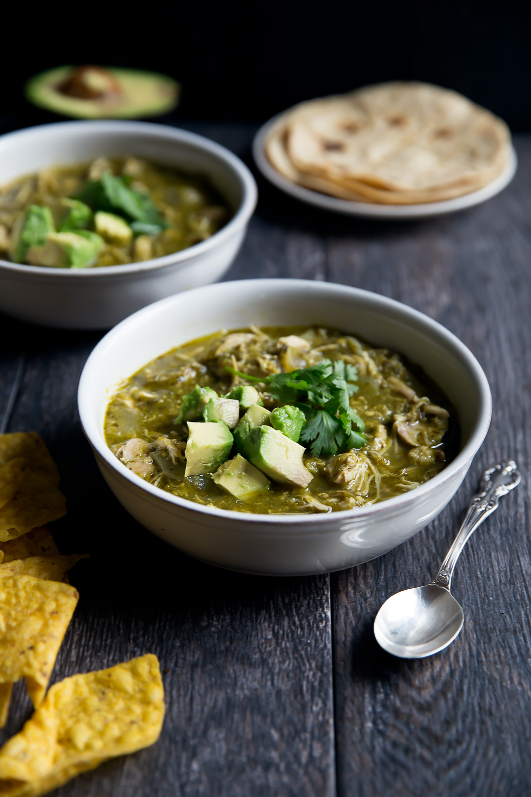 slow cooker chicken chile verde topped with avocado in a bowl