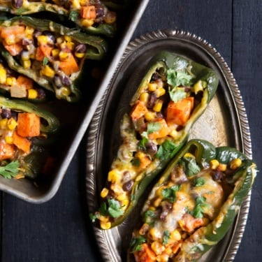 stuffed poblano peppers on a plate and on a baking tray