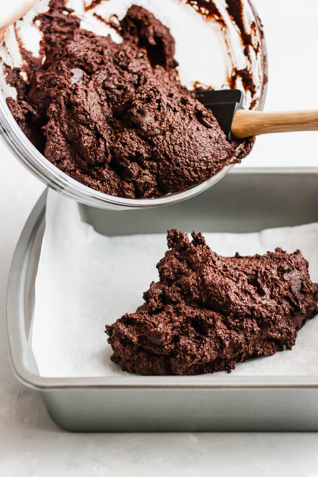 paleo double chocolate banana bread batter being poured into a pan lined with parchment paper