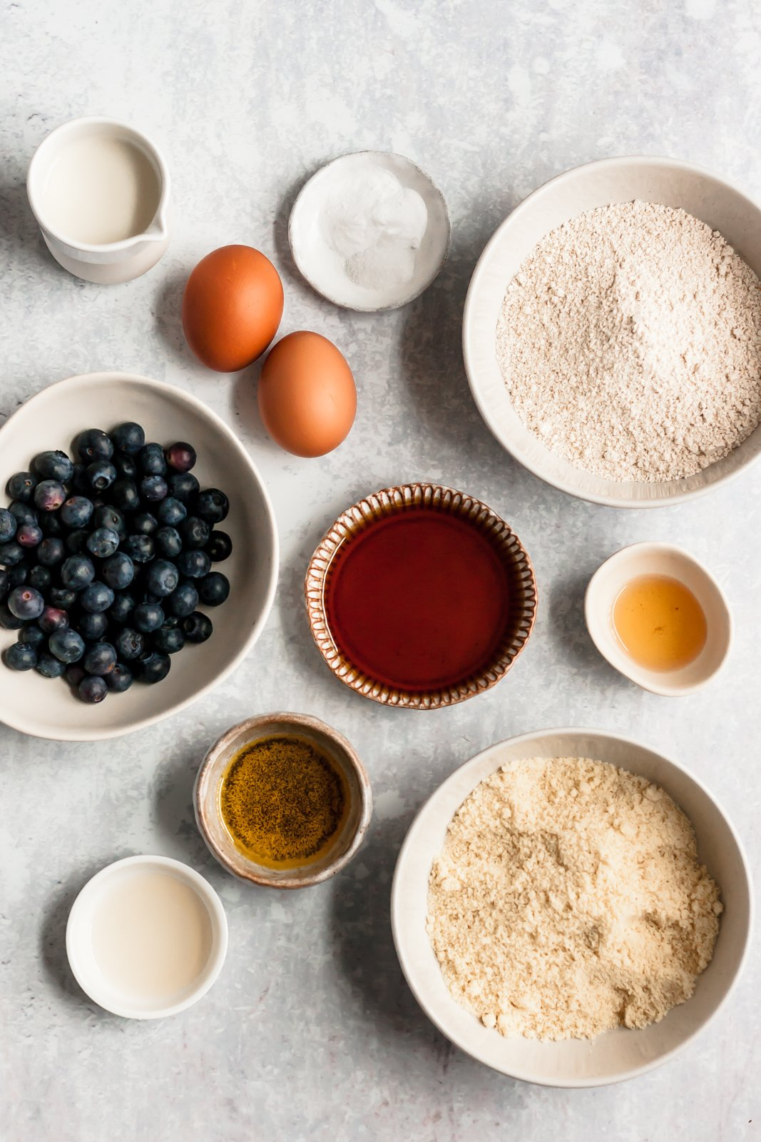 ingredients for healthy blueberry muffins on a grey board