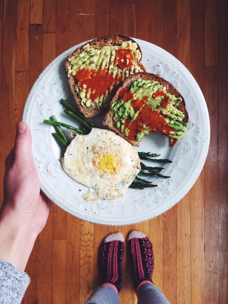 avocado toast with an egg and asparagus on a plate