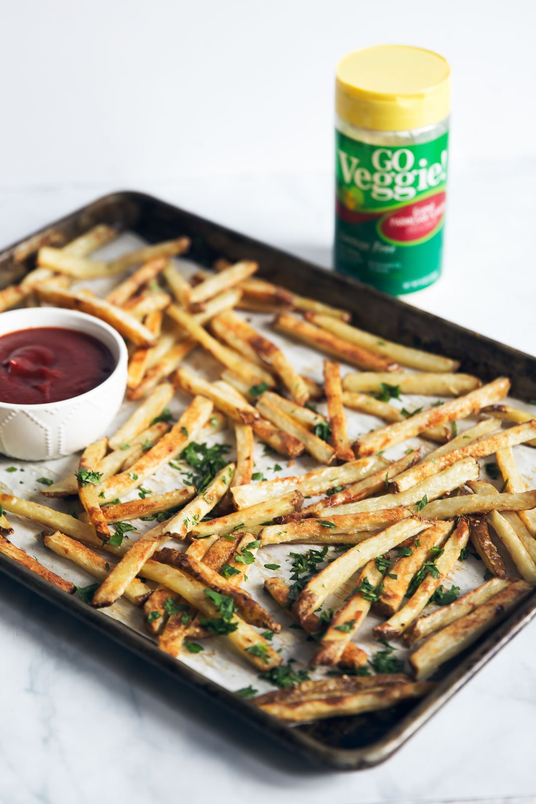 healthy baked french fries on a baking tray with ketchup