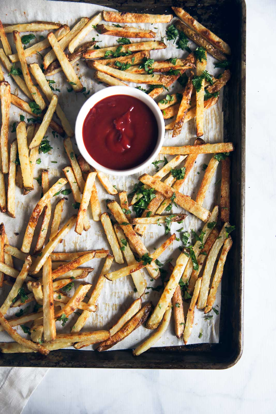 homemade healthy baked french fries on a baking tray with ketchup