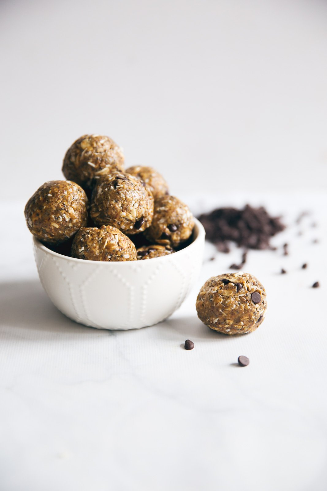 Chocolate chip granola balls in a small white bowl