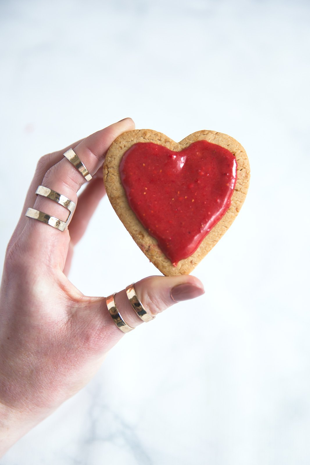 whole wheat sugar cookie in a heart shape with strawberry icing