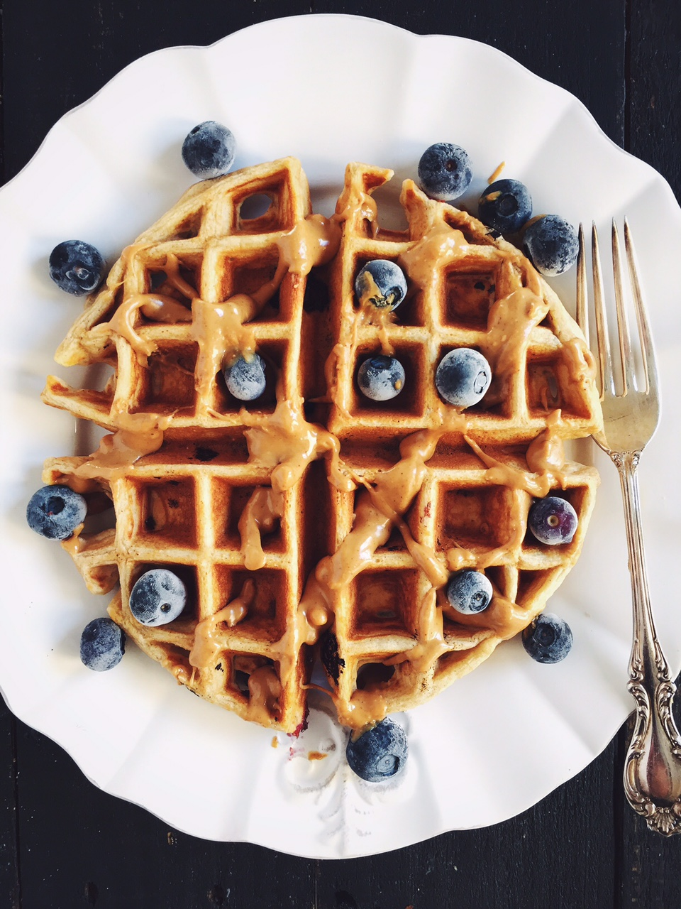 a waffle topped with peanut butter and blueberries