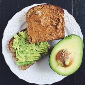 avocado toast and peanut butter toast on a plate with avocado