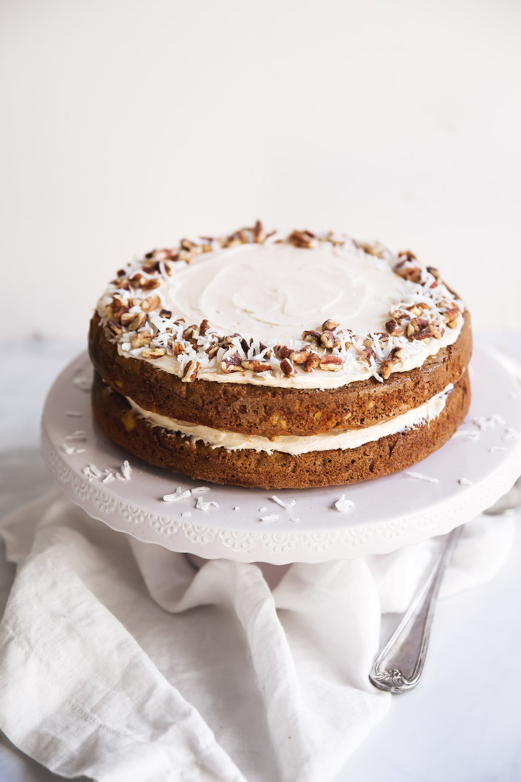 Lightened Up Gluten free carrot cake made from a mixture of almond and oat flour. Topped with a lovely, thick cinnamon cream cheese frosting! Perfect for parties, Easter, or any holiday!