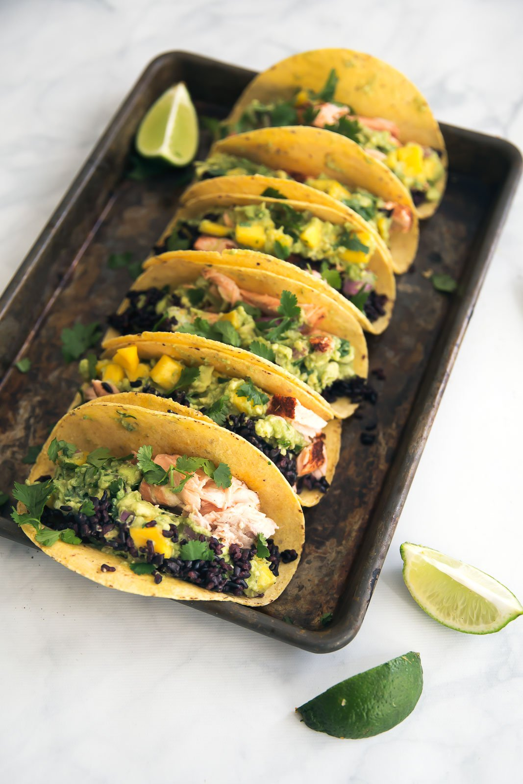 Salmon tacos with black rice and guacamole on a baking sheet