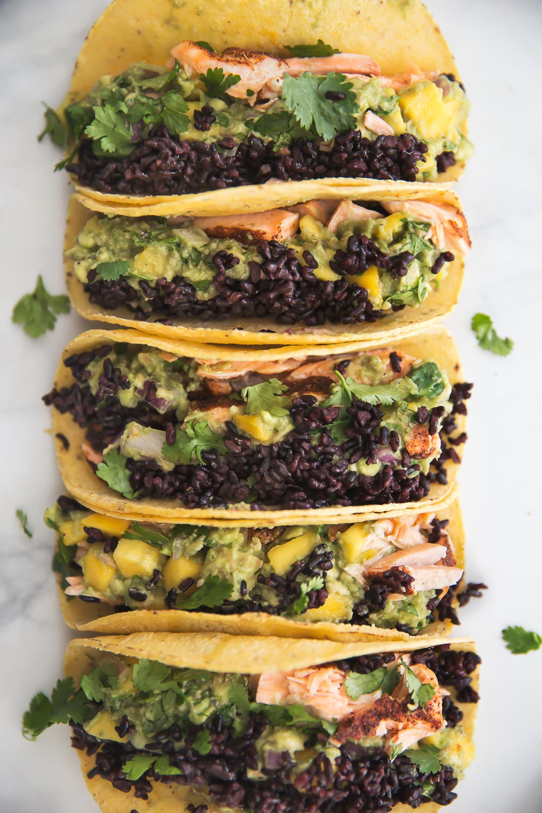 salmon tacos topped with black rice and mango