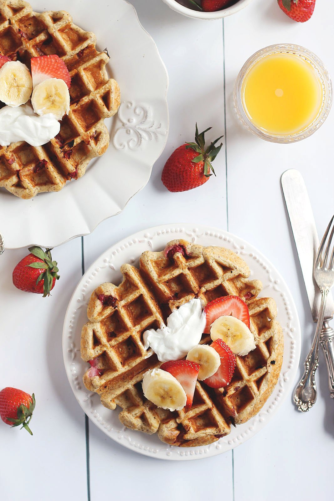 Two waffles topped with strawberries and bananas next to a glass of orange juice