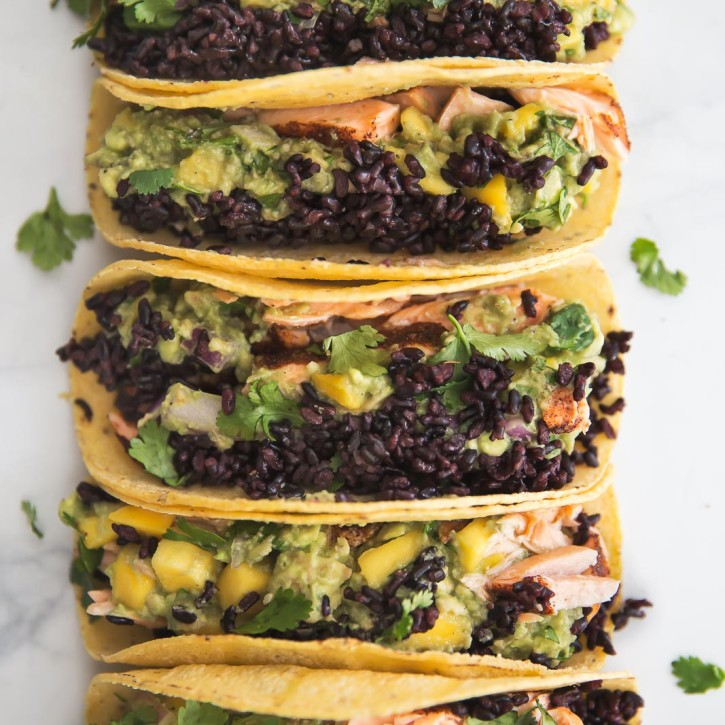 blackened salmon tacos with forbidden rice and mango guacamole in a line