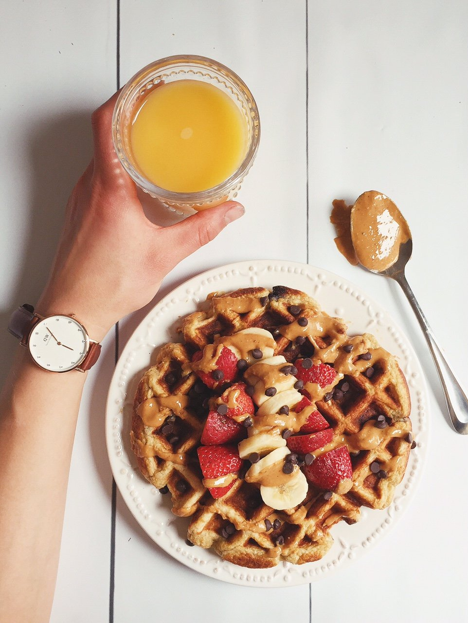 waffle on a plate with a side of orange juice
