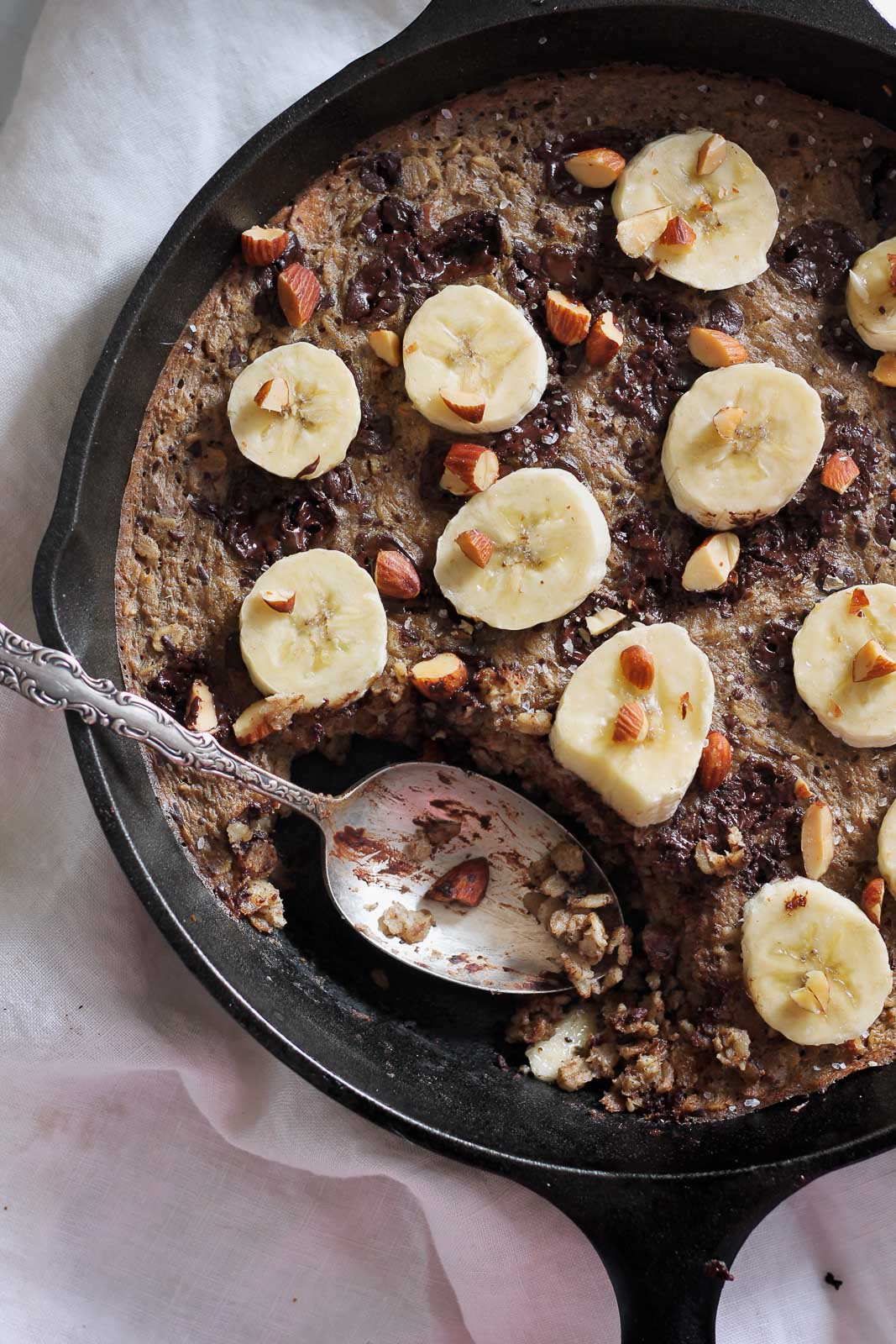 banana baked oatmeal with chocolate and roasted almonds in a skillet