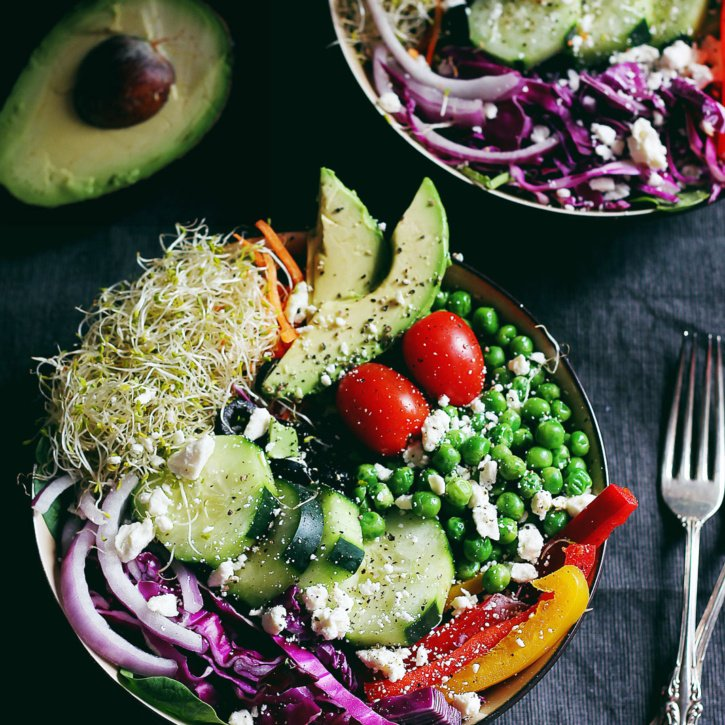 A beautiful & healthy spring green salad with fresh produce, seeds, avocado & the BEST basil lemon vinaigrette. Enjoy as a main meal, bring it to a party, or pack it for lunch!
