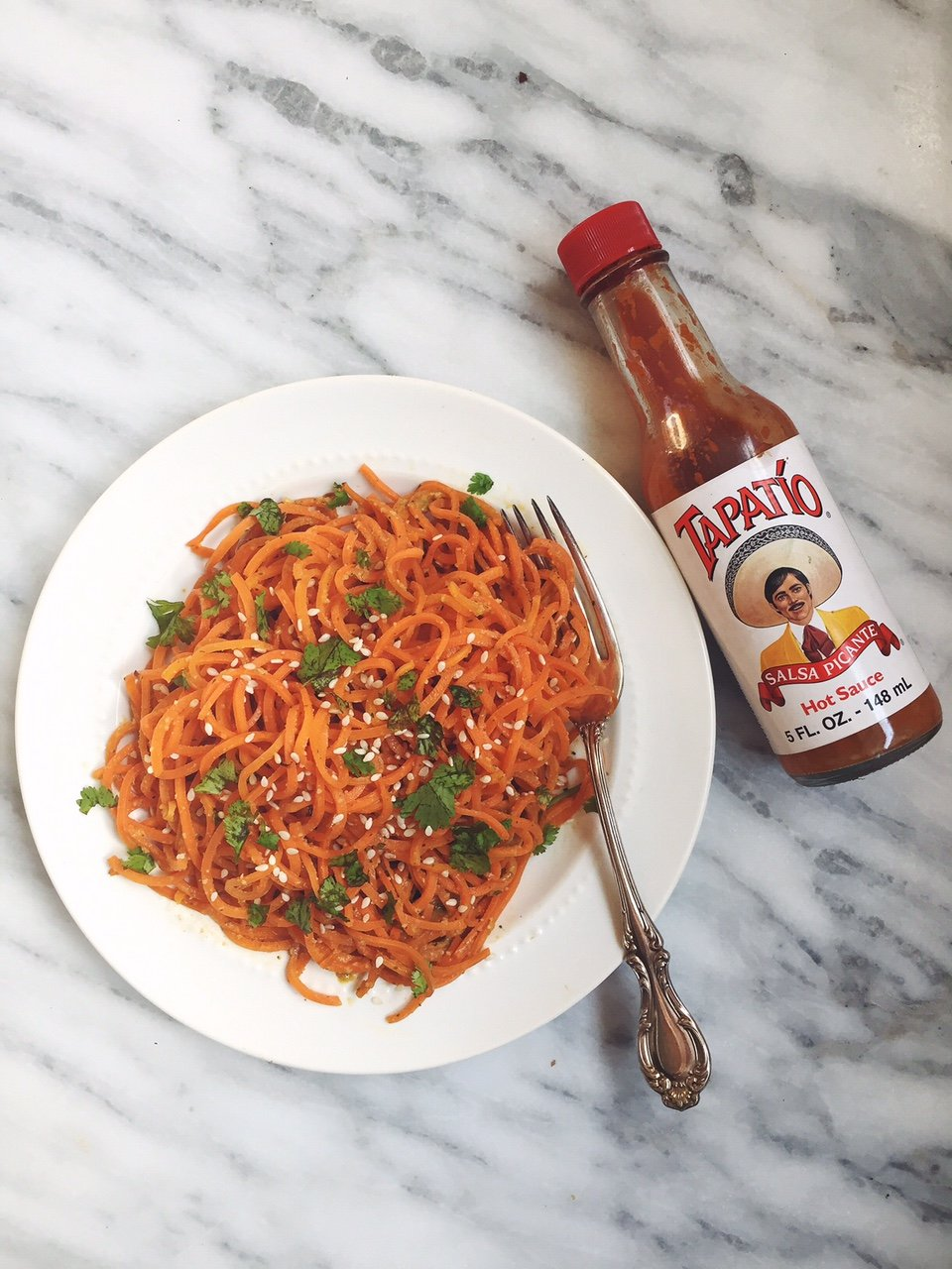 sweet potato noodles on a plate next to hot sauce