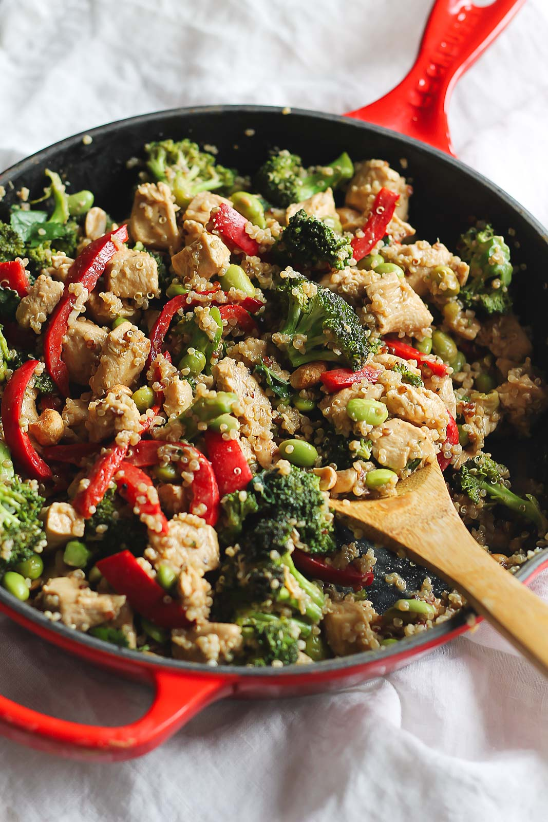 one pan meals: chicken, broccoli, red pepper, and edamame in a red skillet with a wooden spoon