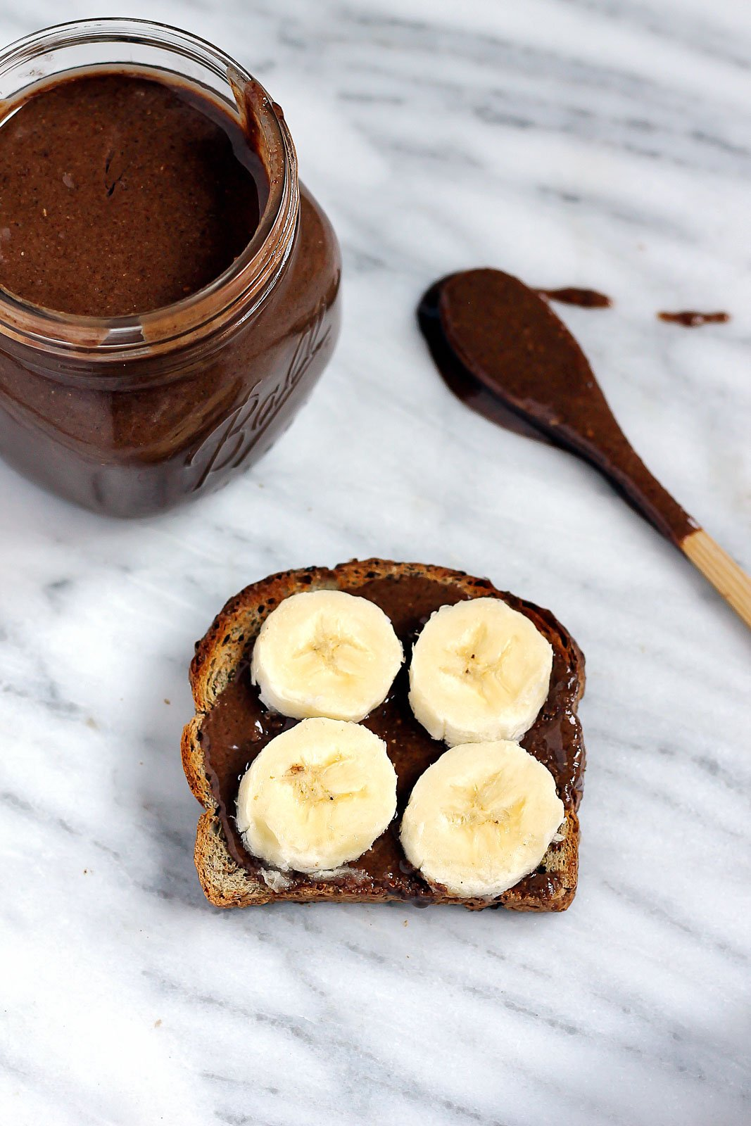 dark chocolate pecan butter in a jar and on toast with banana slices