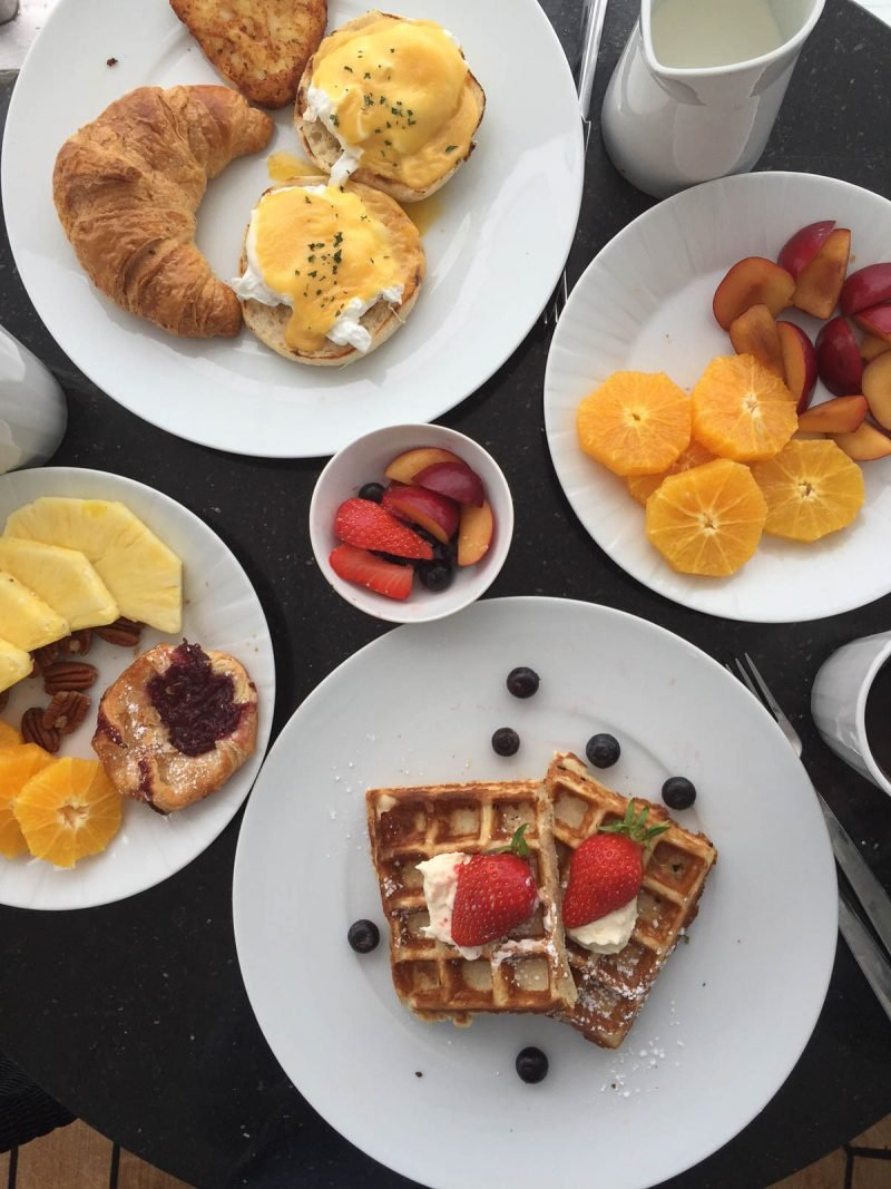 waffles, croissants, fruit, and eggs benedict on plates