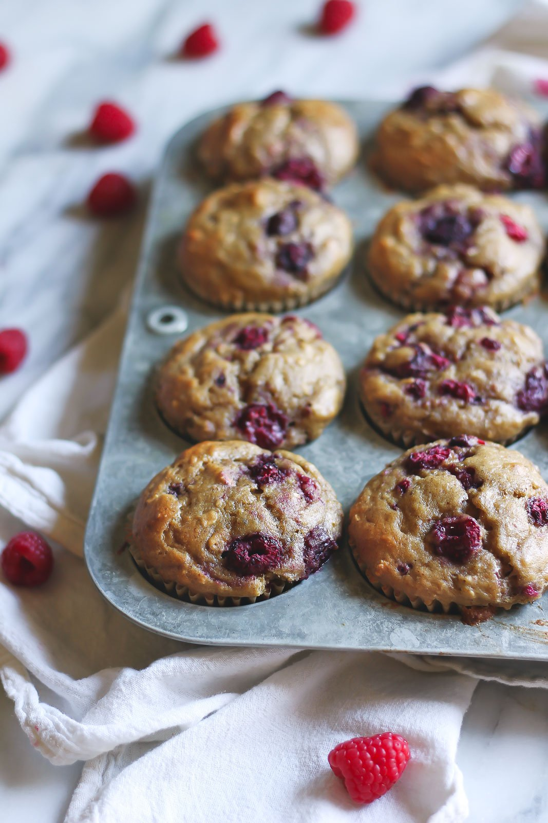 Healthy banana oatmeal muffins bursting with fresh, juicy raspberries! These amazing muffins are made with whole grains, greek yogurt & almond butter -- ingredients you can feel good about!