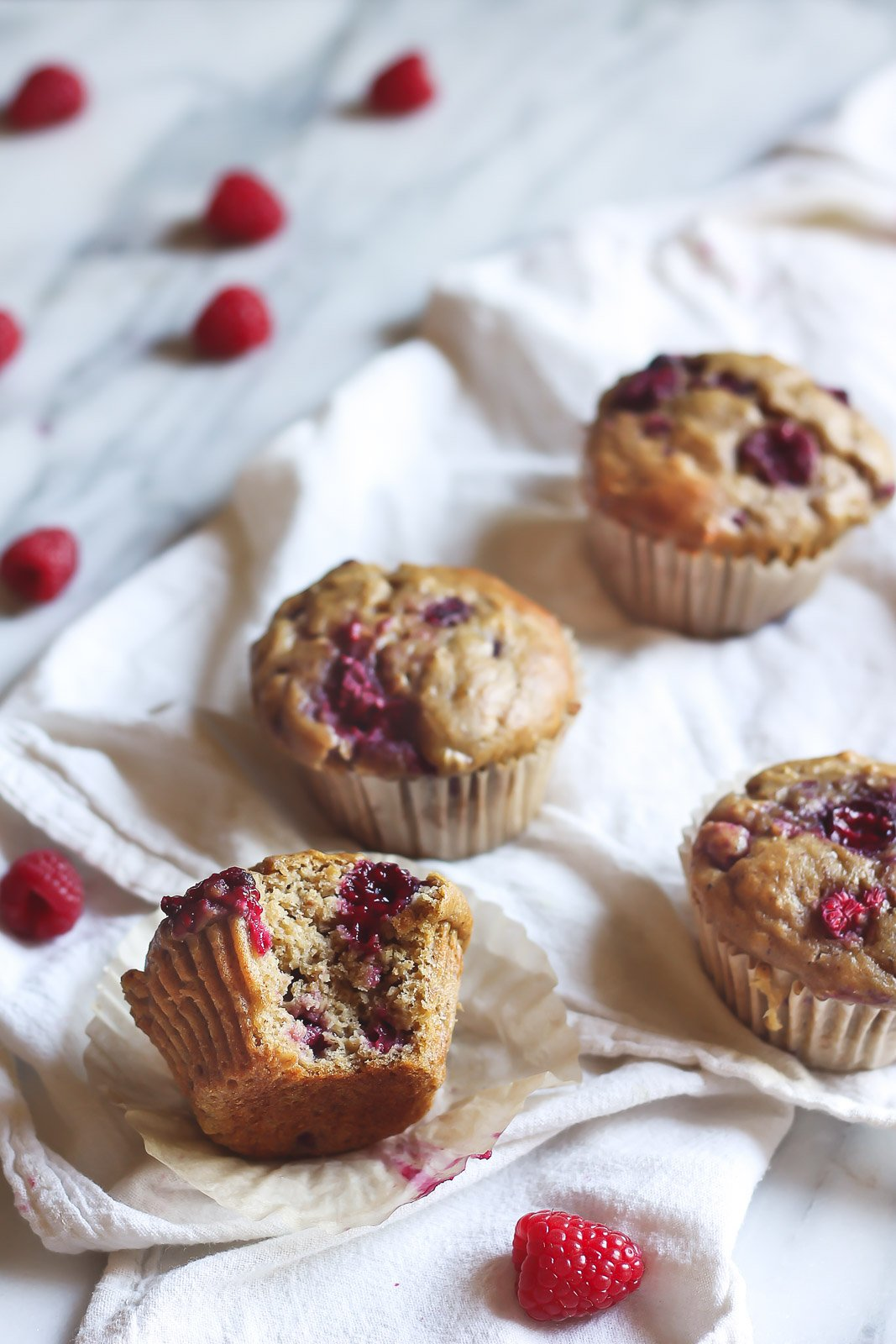 banana oatmeal muffins with raspberries on a linen