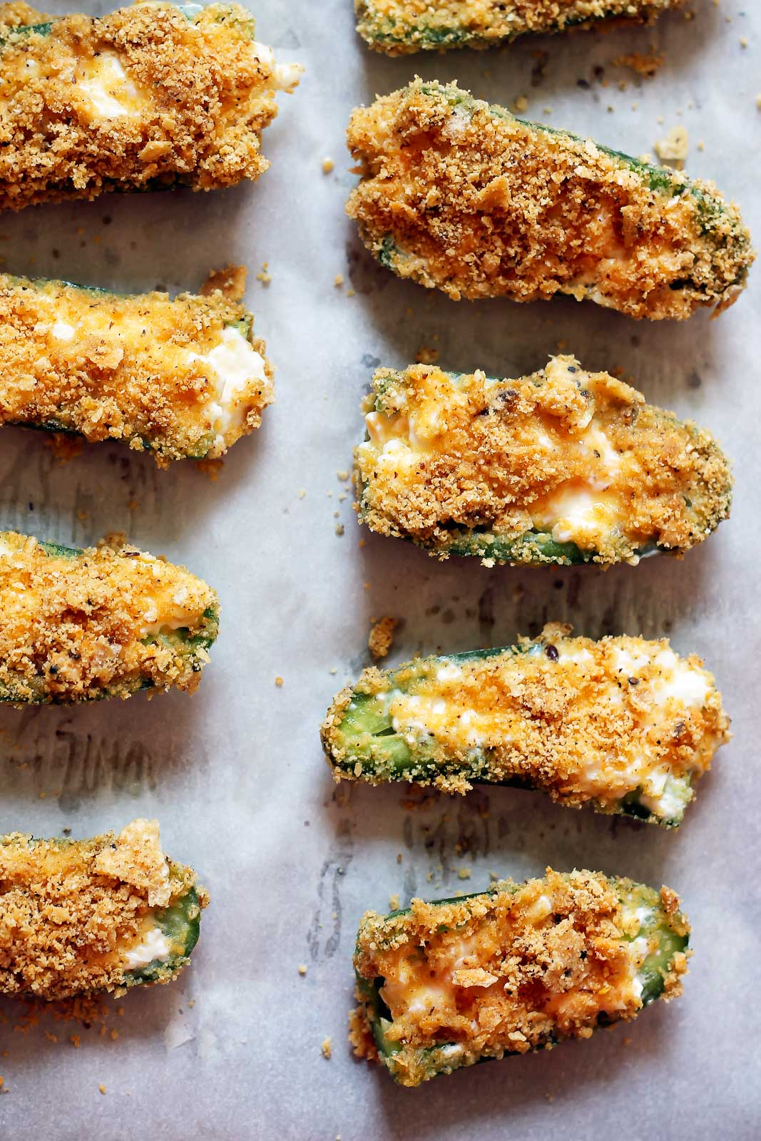 Incredible lightened up baked jalapeno poppers with a sriracha tortilla chip coating! These poppers are a hit for game day or any time you're entertaining. Also great as a snack!