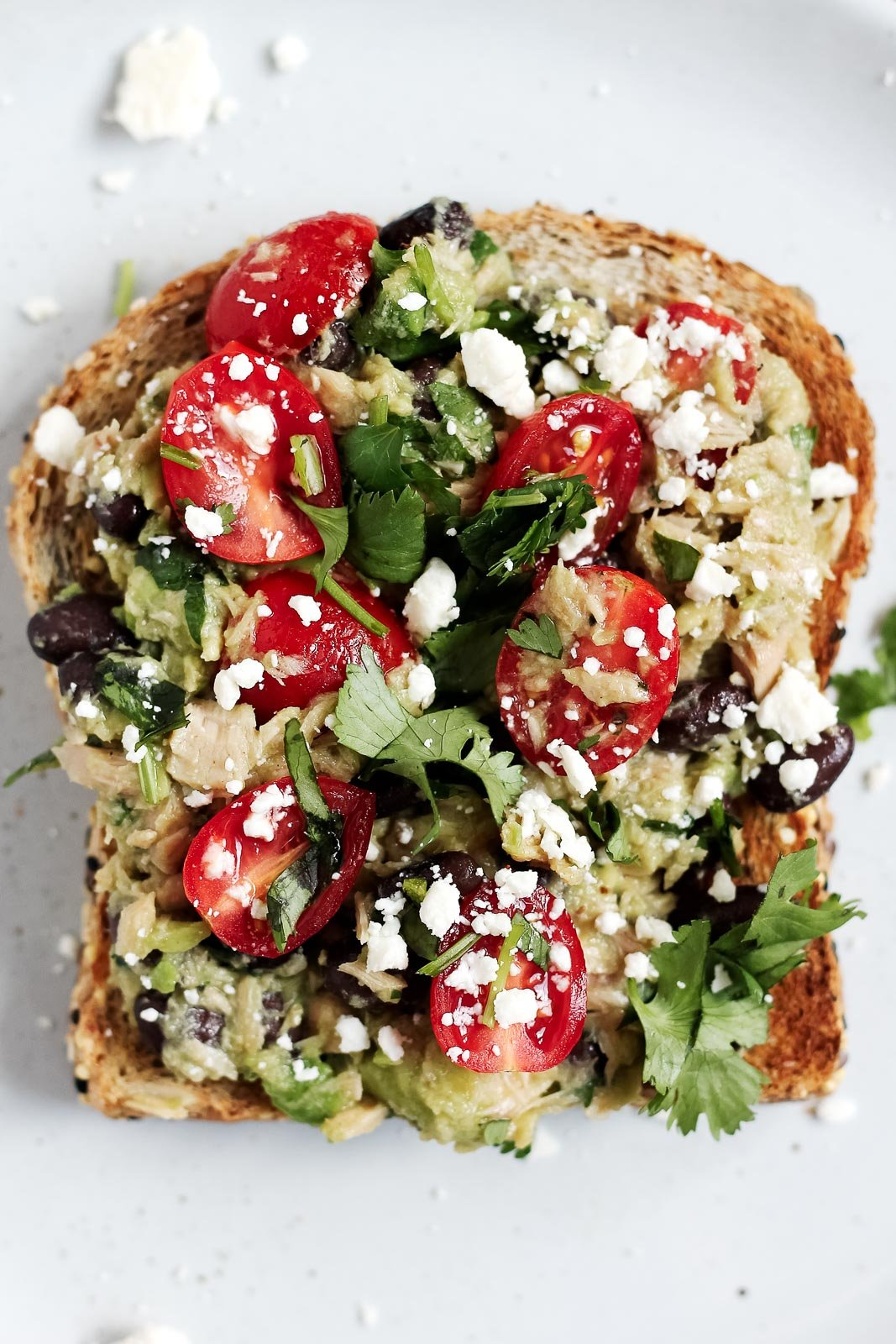 Healthy high-protein avocado tuna salad sandwiches with fiber-rich black beans, tomatoes and cilantro! This recipe takes 5 minutes to make and is a wonderful, healthy no-cook lunch!