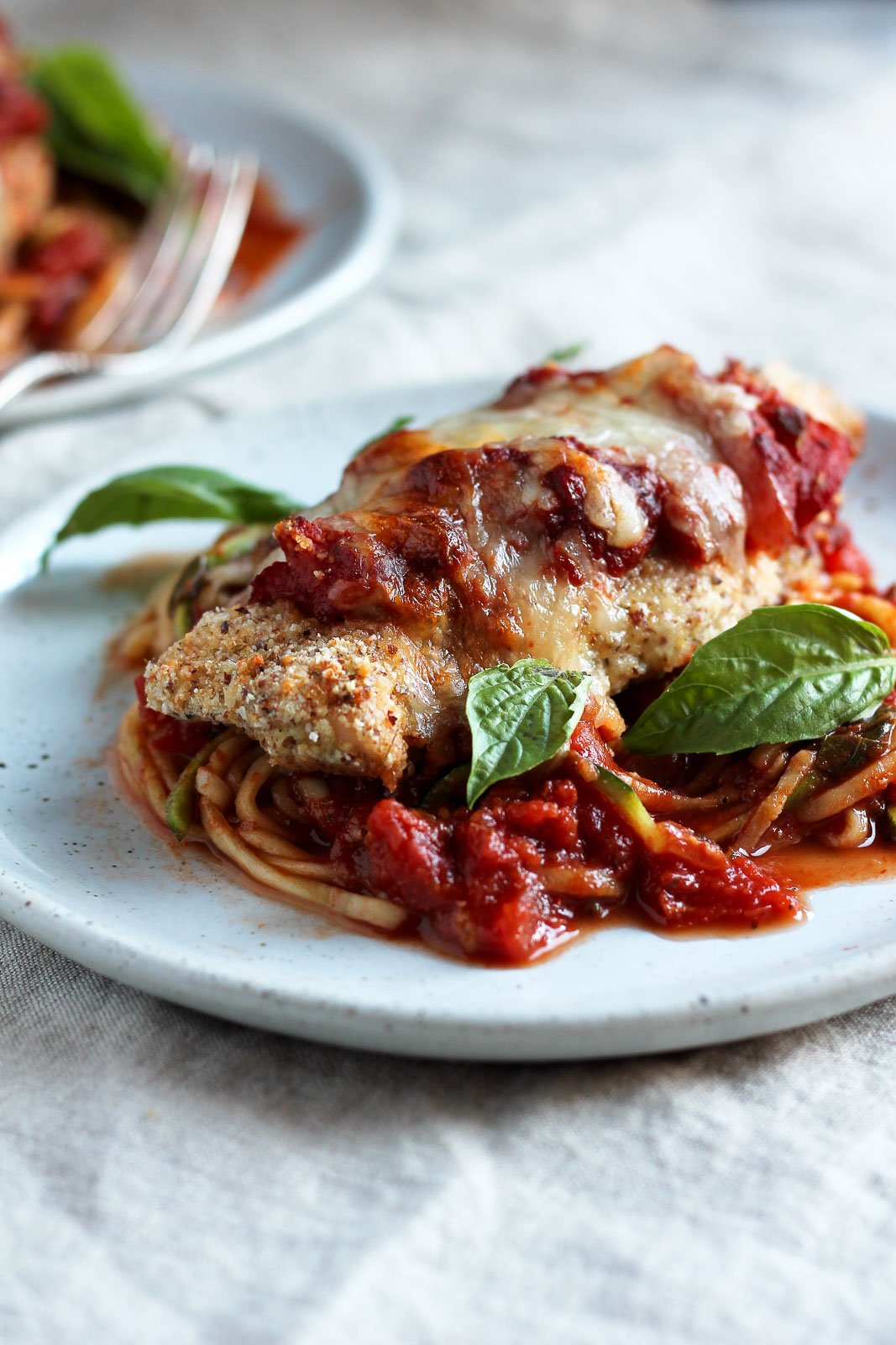 This Healthy Baked Chicken Parmesan is the most amazing comfort food makeover! Serve over zucchini noodles for a low carb, gluten free dinner.