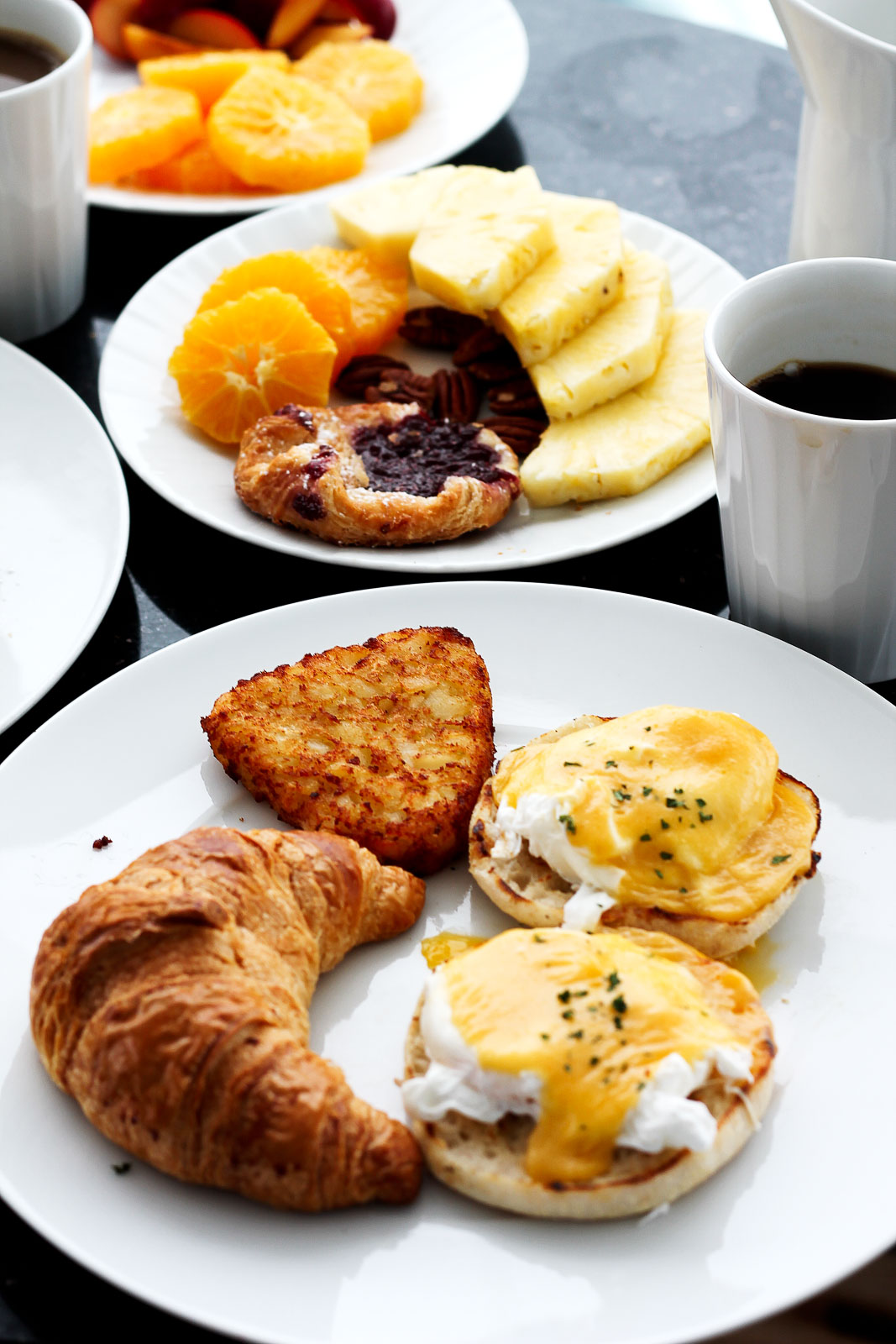 croissant and eggs benedict on a plate