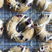 Beautiful whole wheat zucchini donuts bursting with fresh juicy blueberries & drizzled with white chocolate! These are not to be missed.