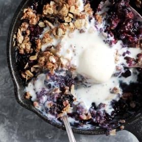 healthy blackberry crisp in a skillet with ice cream
