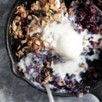 almond flour blackberry crisp in a skillet with ice cream