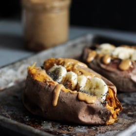Breakfast baked sweet potatoes stuffed with creamy almond butter, banana slices and chia seeds